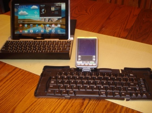 My current tablet and BlueTooth keyboard behind the PDA and foldable keyboard I drafted a novel on in 2003.